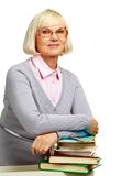 Midage librarian. Pretty elderly lady leaning over a pile of books isolated on white background Stock Photos