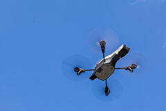 Midair drone shot. A small spy quad copter drone flying over a clear blue sky royalty free stock images