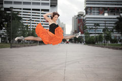 Midair split. Young ballerina practicing a midair split in an urban city setting royalty free stock image