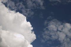 middag Vita stackmolnmoln svävar mot den blåa himlen arkivbilder