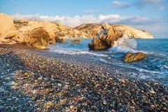 Middagmening van het breken van golven bij het bekiezelde die strand rond Petra tou Romiou, ook als de geboorteplaats van Aphrodi stock foto's
