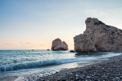 Middagmening van het breken van golven bij het bekiezelde die strand rond Petra tou Romiou, ook als de geboorteplaats van Aphrodi stock fotografie
