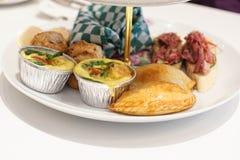Middagthee met miniquiche, gebakjes en sandwiches royalty-vrije stock afbeeldingen