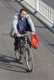Middel-aged man on a bike in city center, Beijing, China. BEIJING – OCTOBER 17, 2011. Middle aged Chinese man cycles in Beijing downtown. From 1995 to 2005 Stock Images