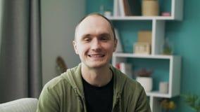 Middel dat van de gelukkige glimlachende jonge Kaukasische mens thuis wordt geschoten stock videobeelden