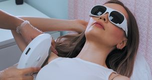 Middel dat van jonge slanke donkerbruine vrouw wordt geschoten terwijl de procedure van de het haarverwijdering van de laseroksel stock video