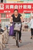 Middel envelheceu a mulher em uma bicicleta na área comercial, Pequim, China Imagem de Stock