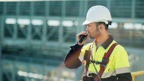 Middel van mannelijke professionele ingenieur wordt geschoten die bouwvakker dragen die gebruikend walkie-talkie die spreken stock footage