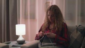 Middel van vrouwenzitting op bank en het breien in comfortabel huis wordt geschoten dat stock video
