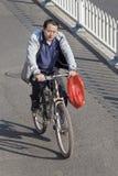 Middel-verouderde mens op een fiets in stadscentrum, Peking, China Stock Afbeeldingen