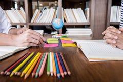 Middelbare school of studentgroepszitting bij bureau in bibliotheek het bestuderen en het lezen, doend thuiswerk en lessenpraktij stock foto