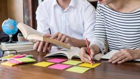 Middelbare school of studentgroepszitting bij bureau in bibliotheek het bestuderen en het lezen, doend thuiswerk en lessenpraktij stock afbeelding