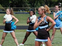 Middelbare schoolcheerleaders hebben prestaties tijdens een voetbalspel stock foto's