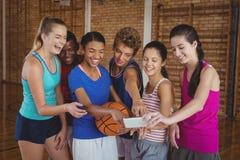 Middelbare schooljonge geitjes die de foto's in de mobiele telefoon bekijken stock afbeelding