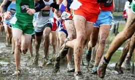 Middelbare schooljongens die dwarsland in de modder rennen Stock Foto's