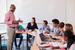 Middelbare schoolleraar Talking To Pupils die Digitale Apparaten in Technologieklasse met behulp van royalty-vrije stock foto