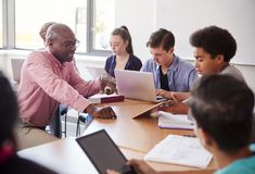 Middelbare schoolleraar Talking To Pupils die Digitale Apparaten in Technologieklasse met behulp van stock foto