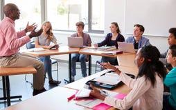 Middelbare schoolleraar Talking To Pupils die Digitale Apparaten in Technologieklasse met behulp van royalty-vrije stock afbeelding
