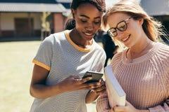Middelbare schoolmeisjes bij universiteitscampus met smartphone royalty-vrije stock fotografie