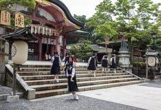 Middelbare schoolmeisjes die schooluniformen dragen bij shrin van Fushimi Inari Stock Afbeeldingen