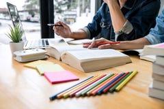 Middelbare schoolpriv?-leraar of studentgroepszitting bij bureau in bibliotheek het bestuderen en het lezen, doend thuiswerk en l stock foto