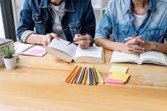Middelbare schoolpriv?-leraar of studentgroepszitting bij bureau in bibliotheek het bestuderen en het lezen, doend thuiswerk en l stock afbeeldingen