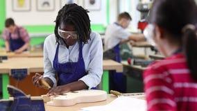 Middelbare schoolstudent de bouwgitaar in houtbewerkingsles stock videobeelden