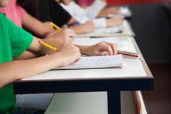 Middelbare schoolstudenten die op papier bij Bureau schrijven Stock Foto's