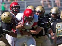 Middelbare schoolvoetbalster die tijdens een Spel worden aangepakt stock foto