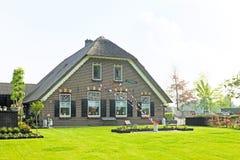Middeleeuws die landbouwershuis met oranje, witte en blauwe fla wordt verfraaid Stock Fotografie