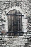 Middeleeuws houten blind bij een venster in een oude steenmuur tallinn stock foto