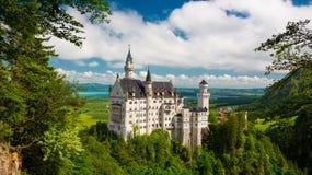 Middeleeuws kasteel Neuschwanstein Rond de blauwe hemel en de Alpen Royalty-vrije Stock Fotografie