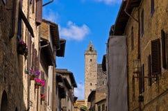 Middeleeuwse die architectuur van San Gimignano, torens en huizen met bloemen, Toscanië wordt verfraaid Stock Foto's