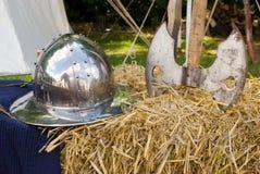 Middeleeuwse helm en bijl op hooi stock foto's