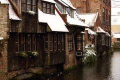 Middeleeuwse houten en baksteengebouwen bij kanaalstraat in Brugge, België De winterlandschap van oude historische stad in Europa stock foto's