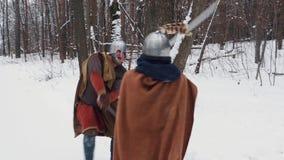 Middeleeuwse Iers en frankish strijders in pantser het vechten in een de winterbos met zwaarden en schilden stock footage