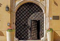 Middeleeuwse ijzerdeur op een steenmuur Stock Afbeelding