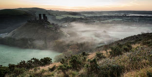 Middeleeuwse kasteelruïnes met mistig landschap bij zonsopgang stock foto's