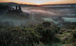 Middeleeuwse kasteelruïnes met mistig landschap bij zonsopgang stock foto