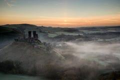 Middeleeuwse kasteelruïnes met mistig landschap bij zonsopgang royalty-vrije stock afbeeldingen