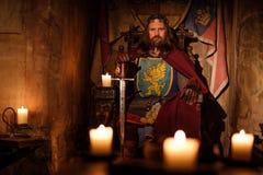 Middeleeuwse koning op troon in oud kasteelbinnenland stock foto's