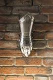 Middeleeuwse metaalhandschoen, detail van een deel van oud pantser, detail van oorlog Glanzende ijzerhandschoen tegen de bakstene royalty-vrije stock fotografie