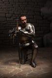 Middeleeuwse ridder die met zwaard knielen Royalty-vrije Stock Foto's