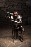 Middeleeuwse ridder die met zwaard knielen Royalty-vrije Stock Fotografie
