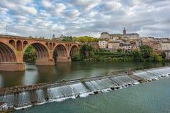 Middeleeuwse rivieroeverstad met een baksteenbrug en een kleine gemaakte mens stock afbeelding