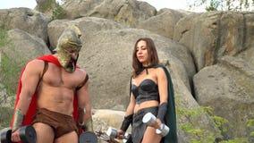 Middeleeuwse strijder in het uitwerken in het hout met zijn vrouw stock videobeelden