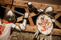 Middeleeuwse strijders in ijzerpantser het vechten met zwaarden Stock Afbeeldingen