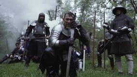 Middeleeuwse strijders in metaal chainplate pantser in het bos onder regen stock videobeelden