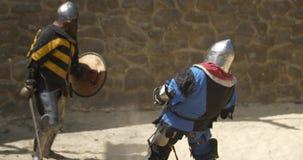 Middeleeuwse toernooien Twee sterke strijdersridders die bij arena vechten stock videobeelden