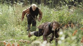 Middeleeuwse Vikingen voeren onderzoek van het grondgebied in het bos uit stock video
